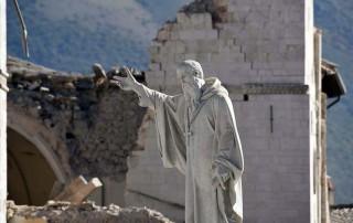 A staue before a church crumbled by earthquakes